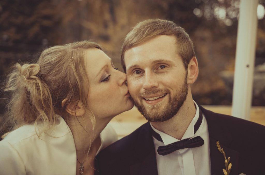 Die Braut küsst den Bräutigam auf die Wange