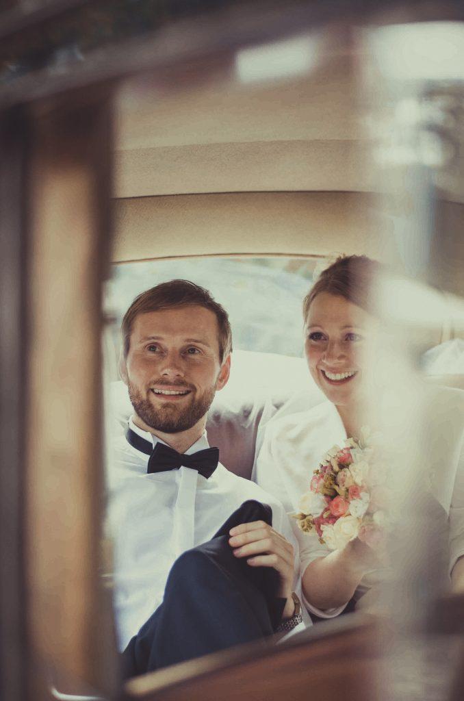 Ein Brautpaar sitzt im Auto