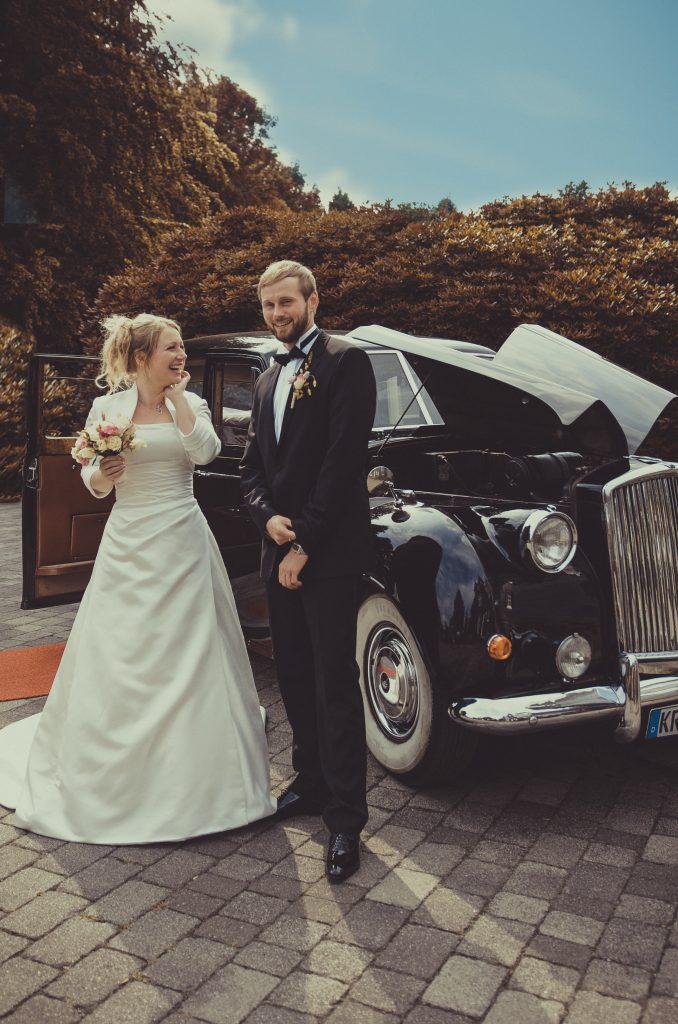 ein Hochzeitspaar steht vor dem auto