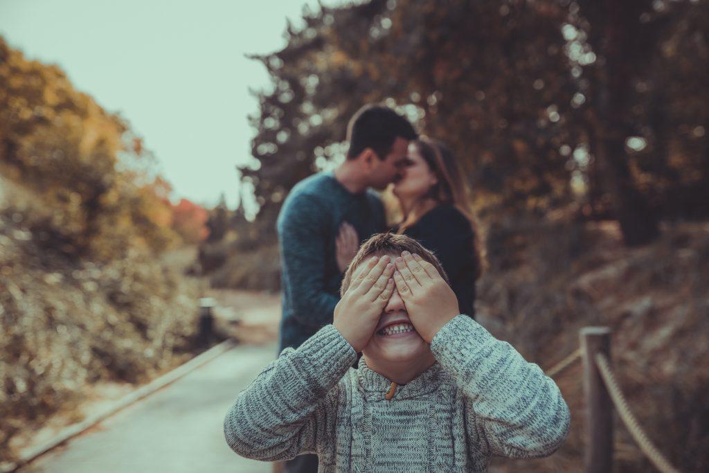 Kind hält sich die Augen zu während die Eltern im Hintergrund knutschen