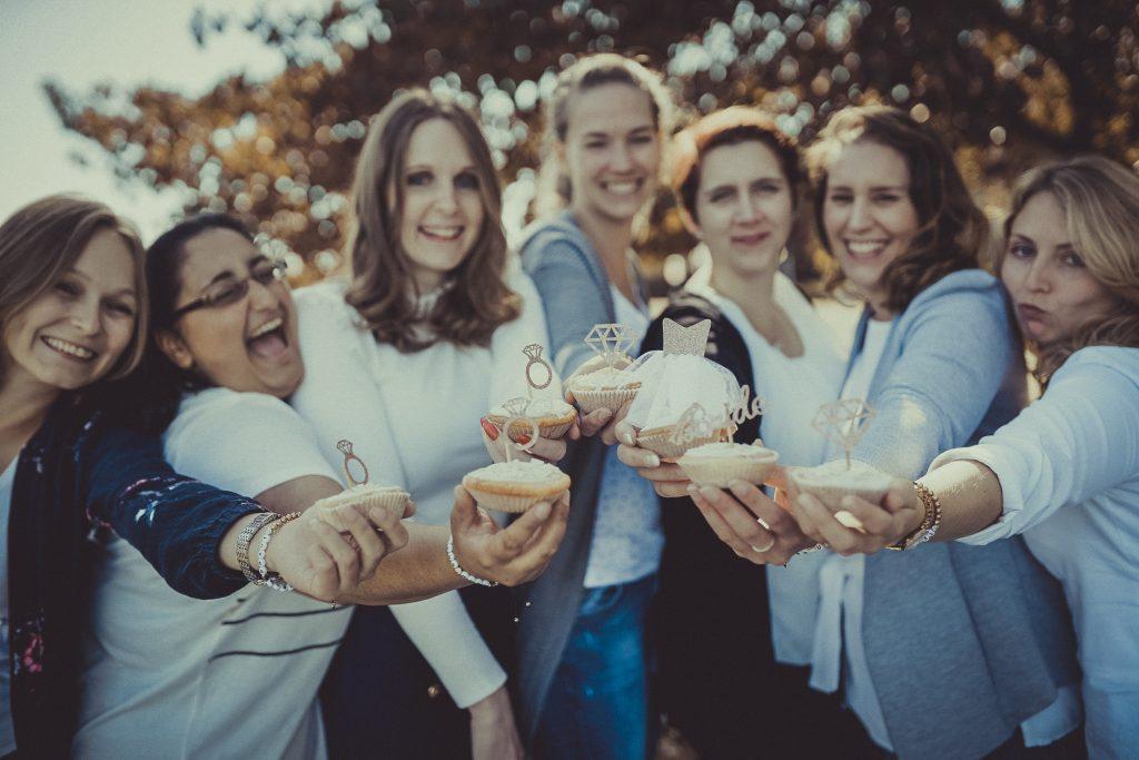 frauen stehen mit cupcakes in Düsseldorf und feiern den Junggesellenabschied