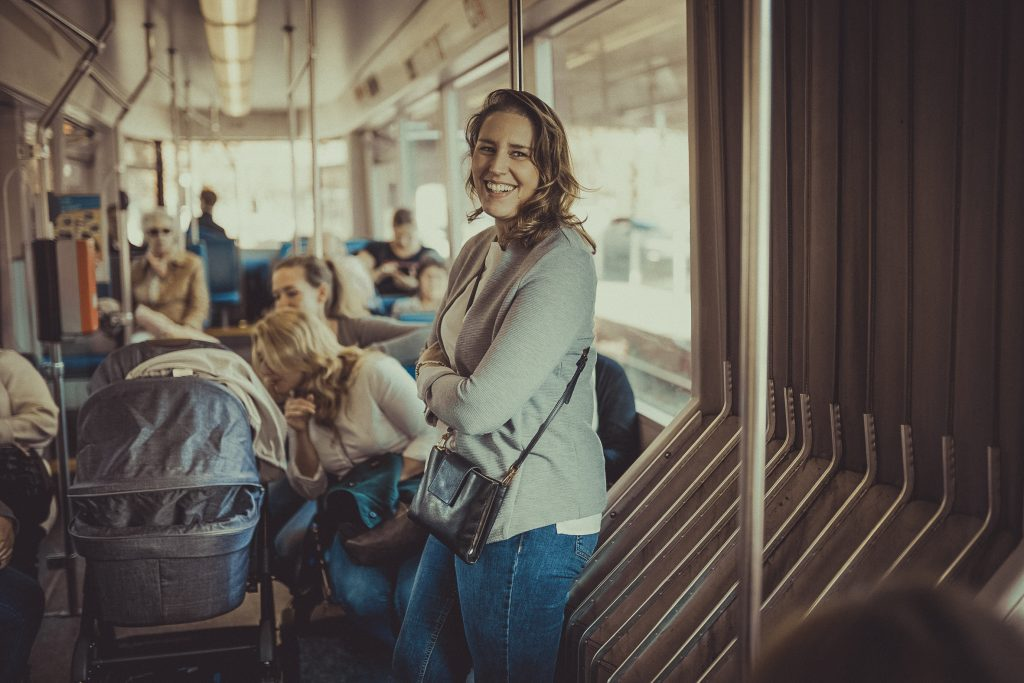 Frau lacht und steht in der Straßenbahn