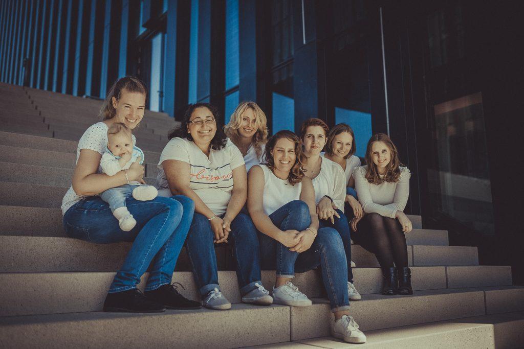 Frauen feiern den Junggesellenabschied und sitzen auf einer Treppe in Düsseldorf