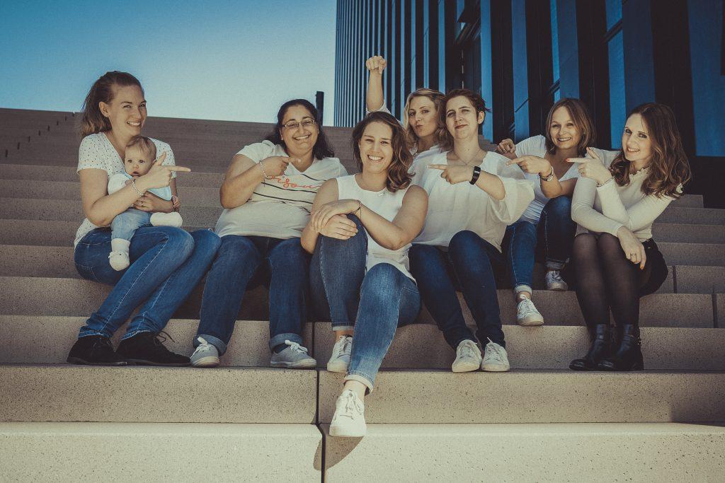 frauen sitzen auf einer Treppe und feiern den Junggesellenabschied
