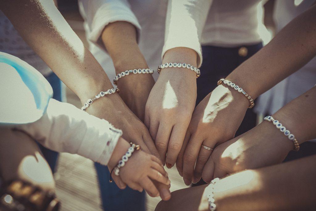 Frauen halten die Hände zusammen und feiern den Junggesellenabschied