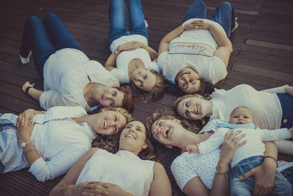 Frauen liegen im Kreis und lachen