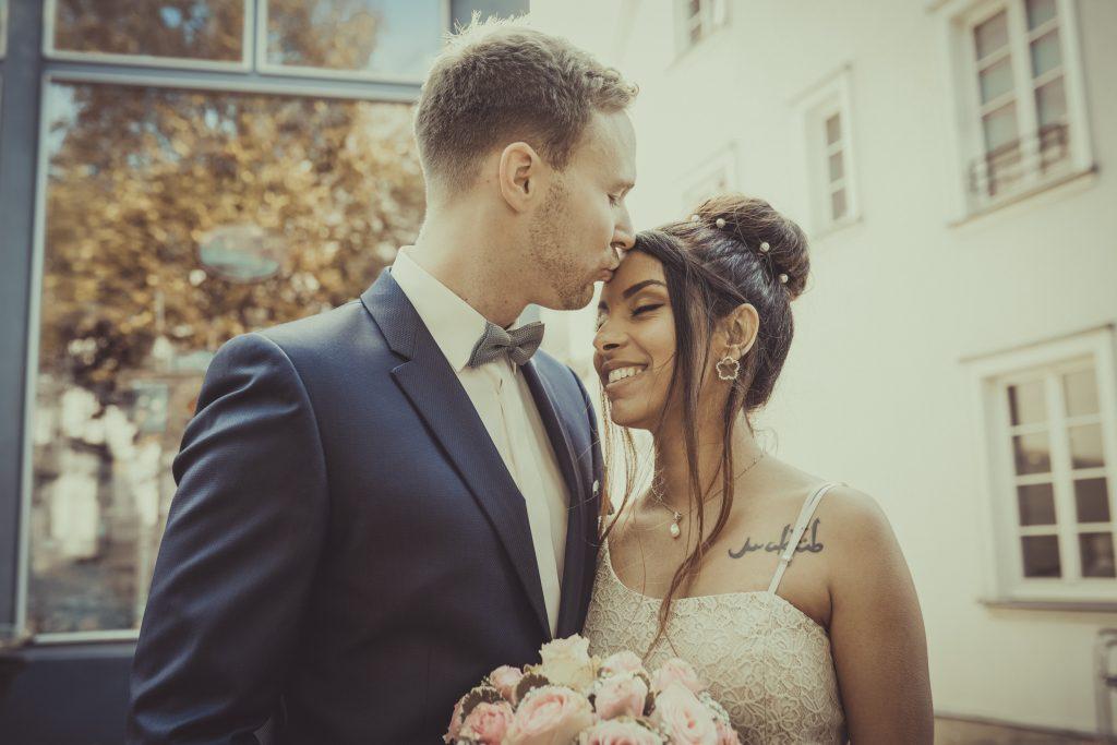 Bräutigam küsst die Braut auf die Stirn