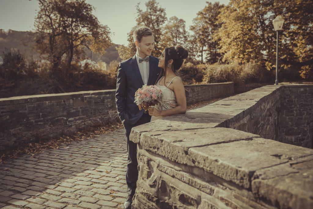 braut und Bräutigam stehen auf einer Brücke and der Ruhr