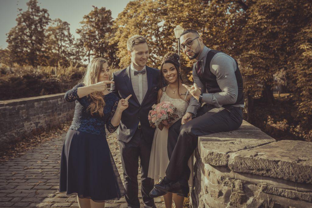 Brautpaar und Trauzeugen zeigen auf das Brautpaar
