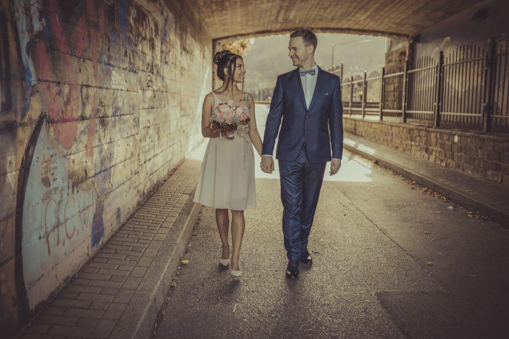 Brautpaar geht Hand in Hand unter eine Unterführung