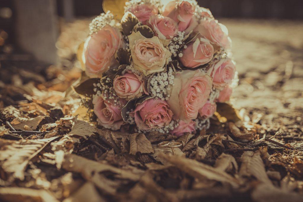 Brautstrauß liegt auf herbstlichen Blättern hinter Hochzeitsringen