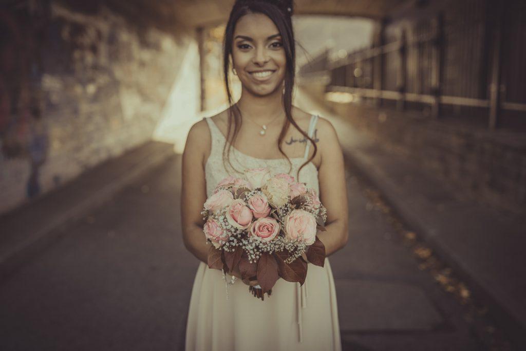 Braut steht mit einem Hochzeitsstrauß unter einer Unterführung