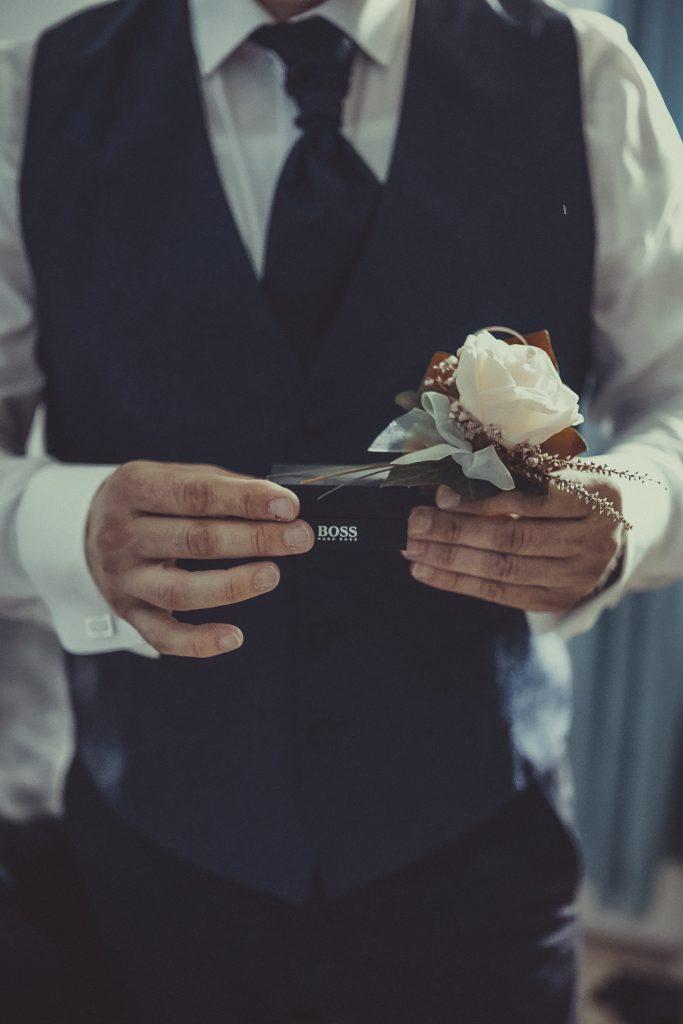 Bräutigam hält die Manschettenköpfe