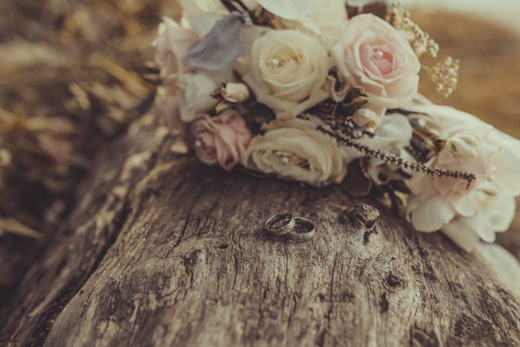 Hochzeitsblumenstrauß mit Ringen auf Holz