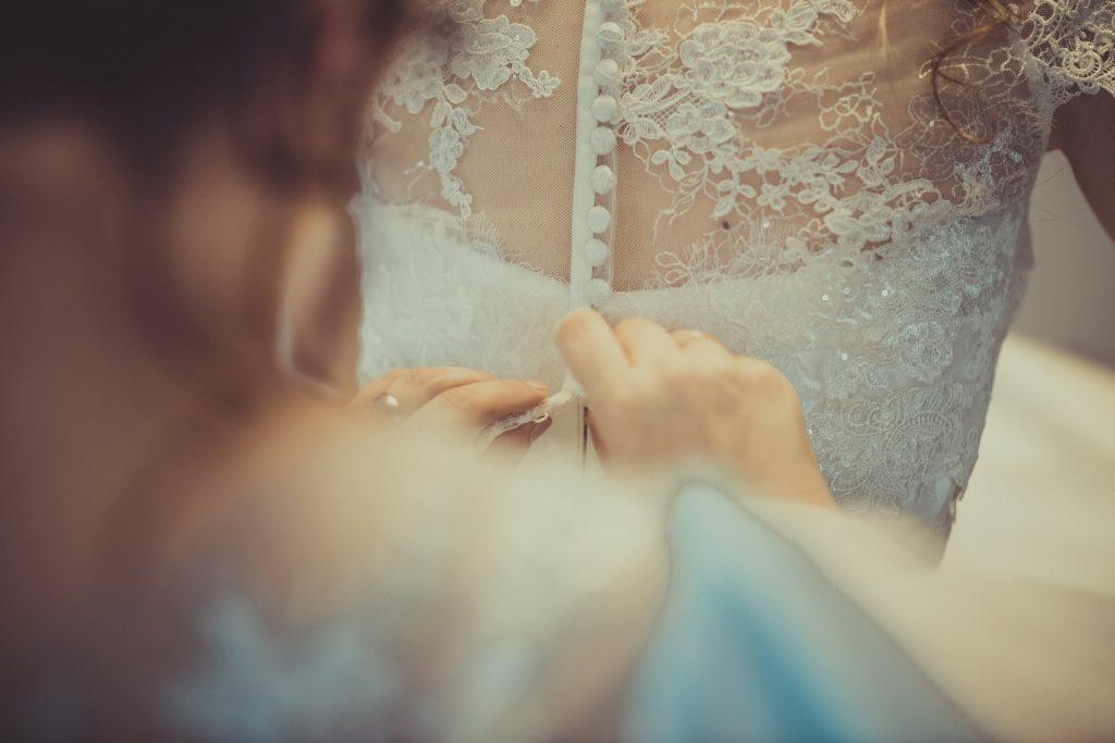 Trauzeuge knöpft der Braut das Hochzeitskleid zu