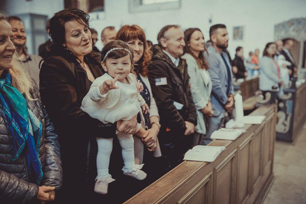 Patentante hält das Taufkind in der Kirche