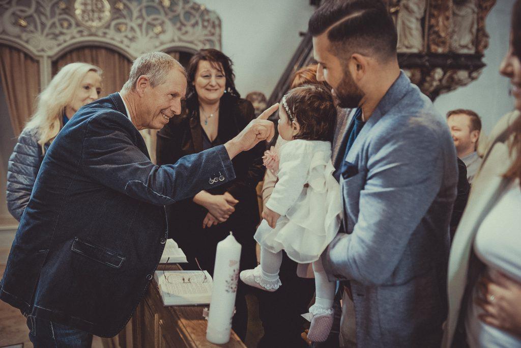 Patenonkel segnet das Taufkind