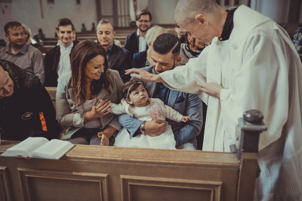 Priester oder Pfarrer segnet das Kind