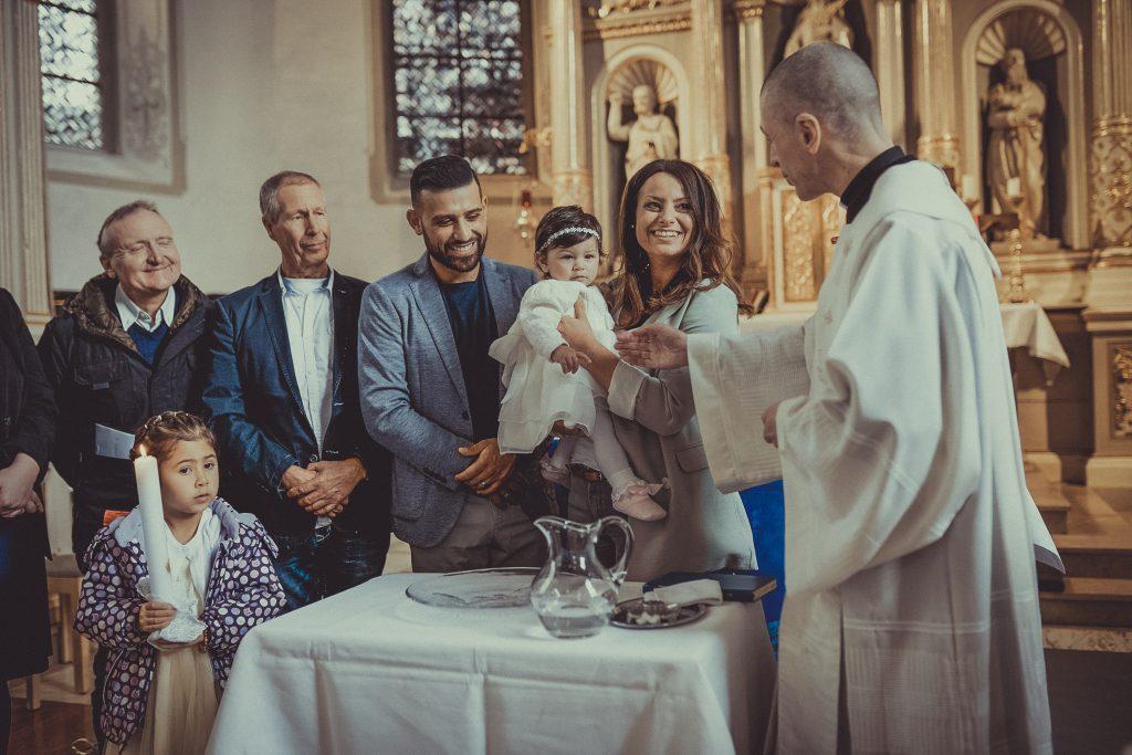 Priester oder Pfarrer gratuliert den Taufeltern zur Taufe und tauft das Kind