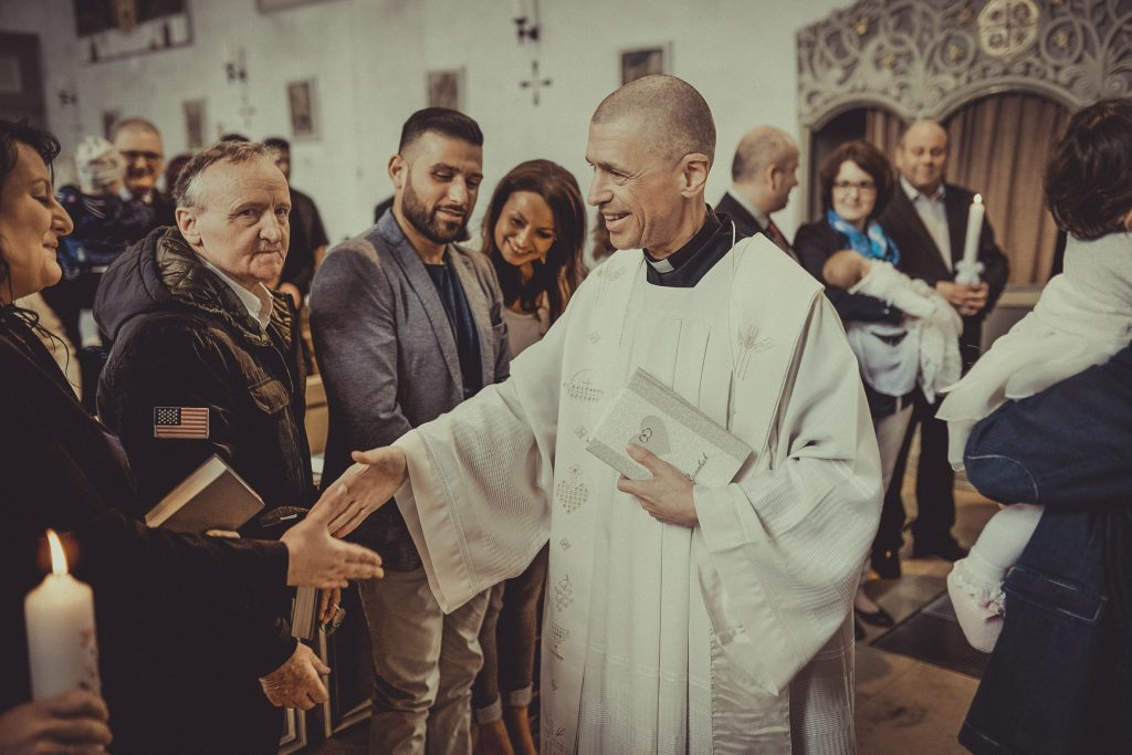 Priester oder Pfarrer gratuliert den Taufeltern zur Taufe