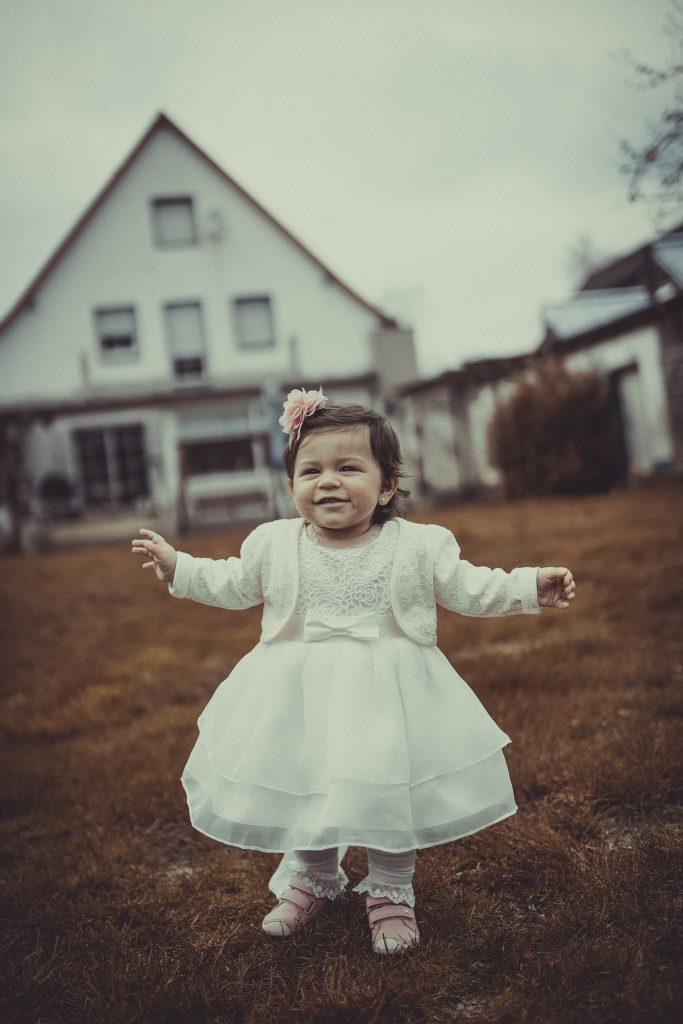 Taufkind läuft mit Taufkleid und Taufschleife