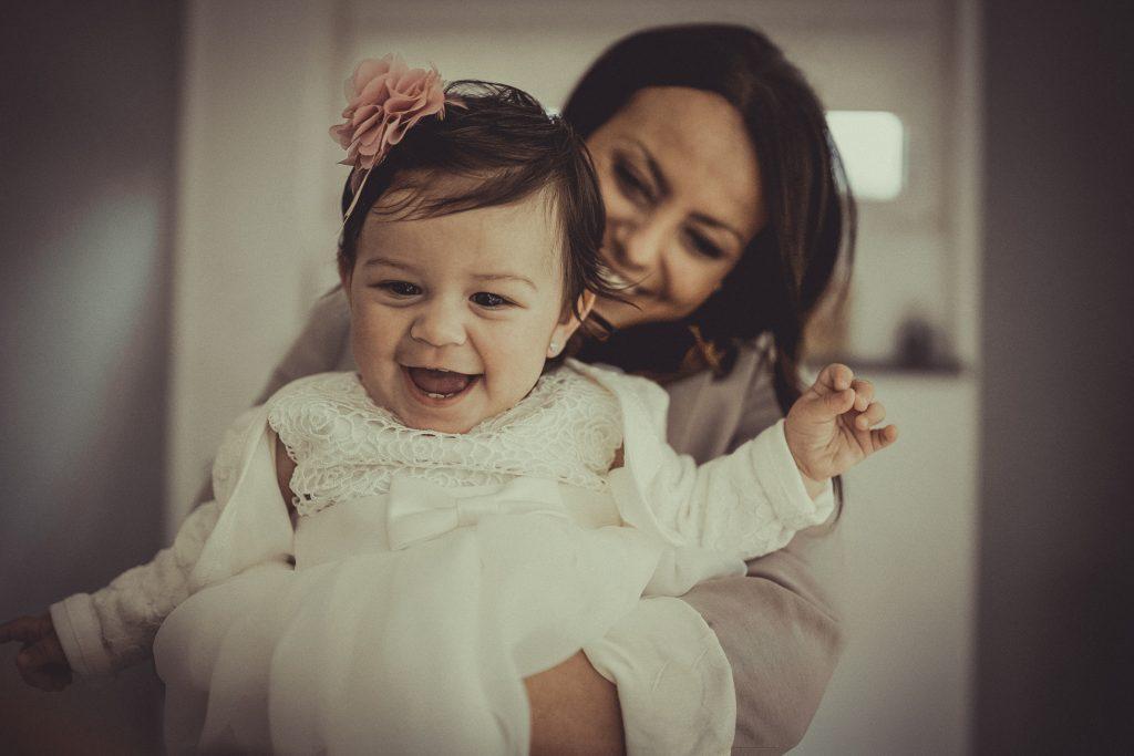 Taufkind lacht in den Armen der Mutter