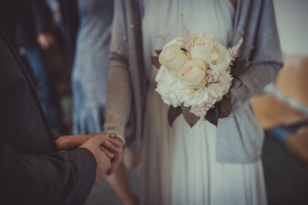 Braut hält den Brautstrauß und hält die Hand vom Bräutigam