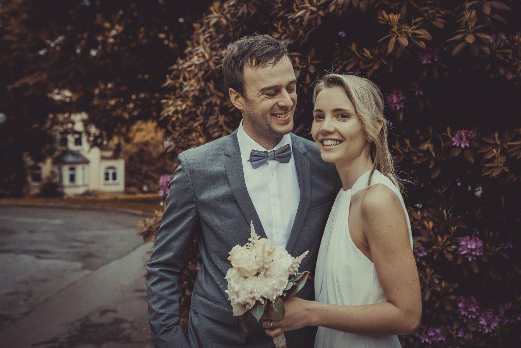Brautpaar steht vor einem Rhododendron Strauch vor dem Standesamt Essen