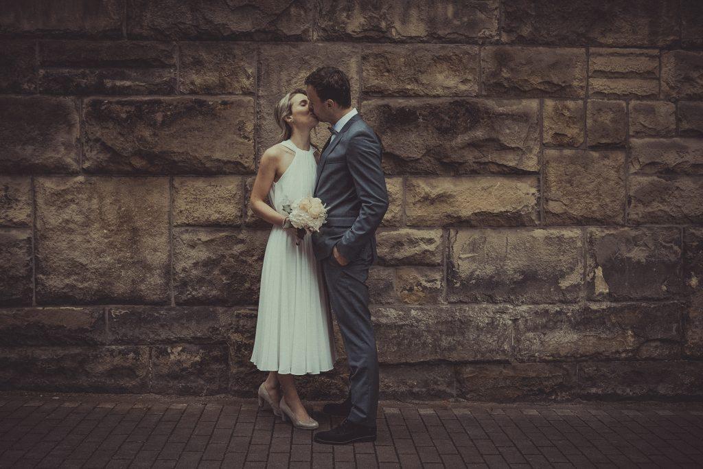 Brautpaar steht vor einer Wand und küsst sich