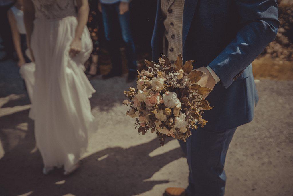 Bräutigam hält den Blumenstrauß