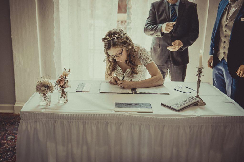 Brautpaar unterschreibt im Standesamt Witten