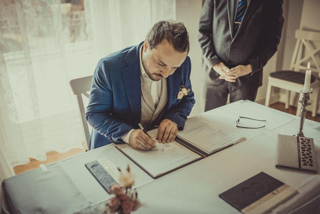Bräutigam unterschreibt im Standesamt Witten