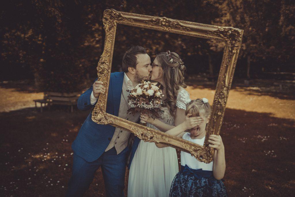 Brautpaar küsst sich und hält einen Bilderrahmen