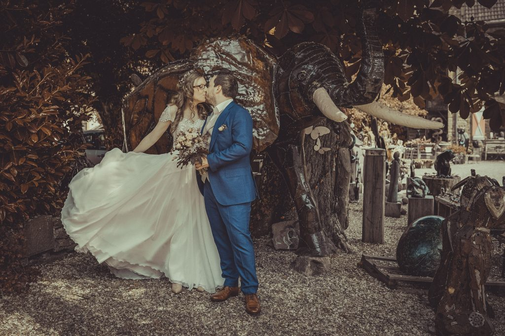 brautpaar küsst sich vor einem Elefanten aus Metall