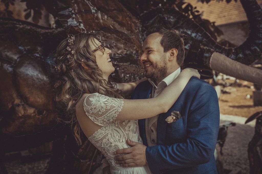 Brautpaar lacht sich vor einem Elefanten aus Metal an