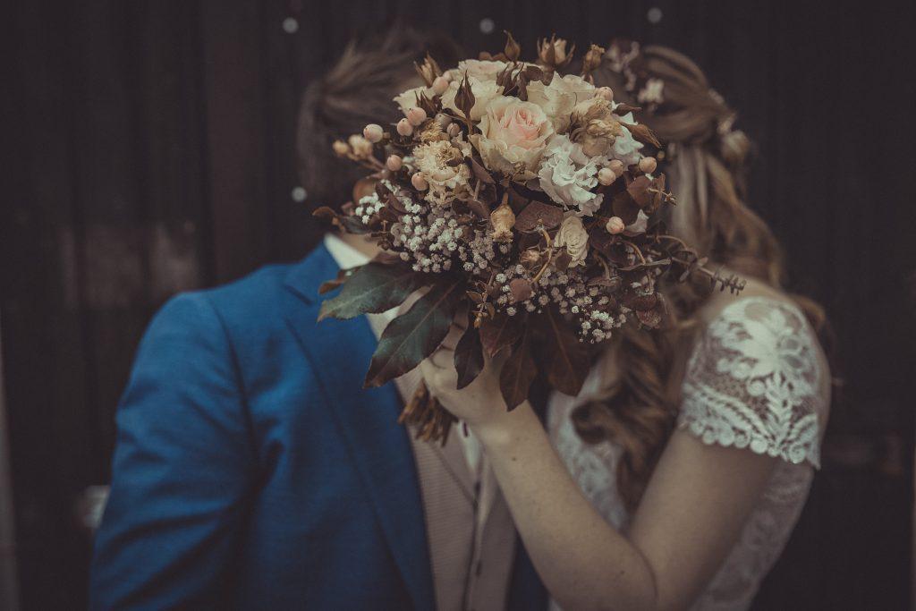 Brautpaar küsst sich hinter einem Brautstrauß