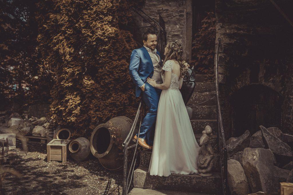 Brautpaar lächelt sich auf einer Treppe an