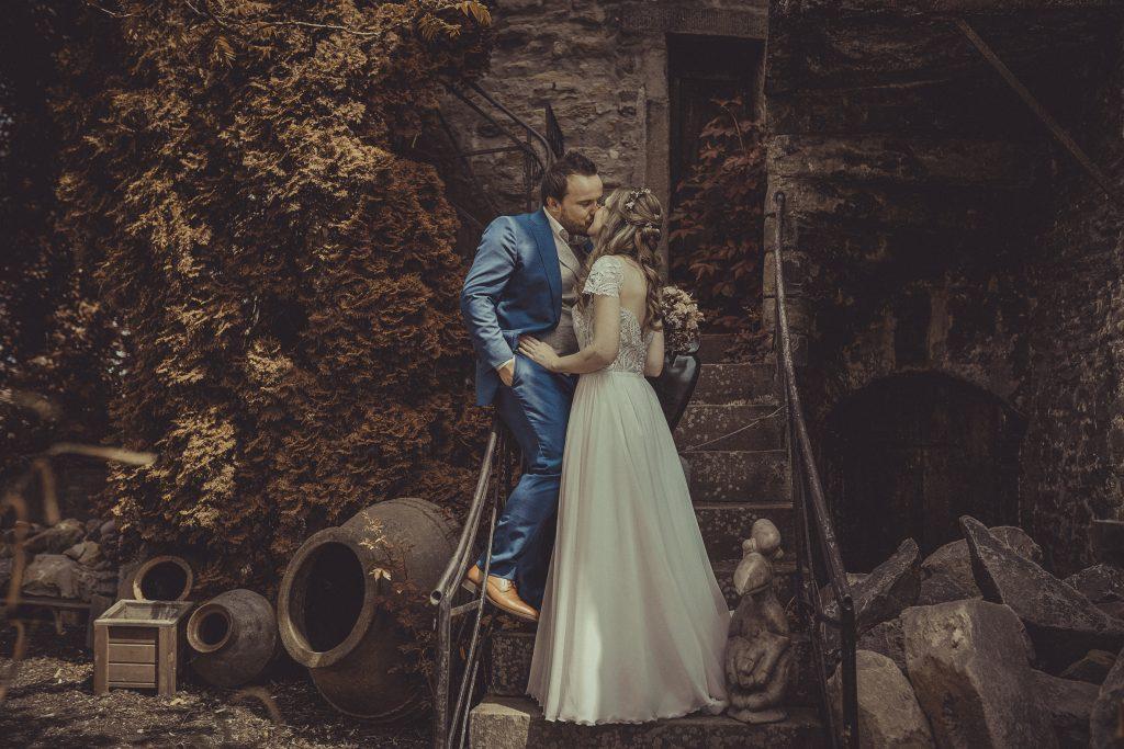 Brautpaar küsst sich auf einer Treppe