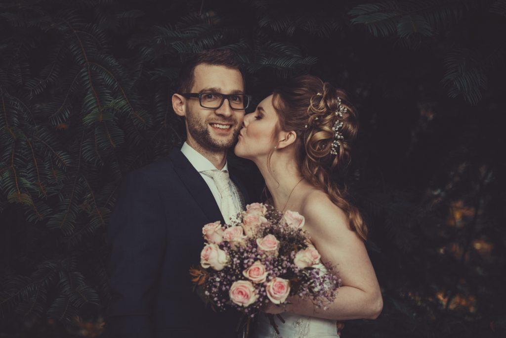 Braut küsst bräutigam auf die Wange