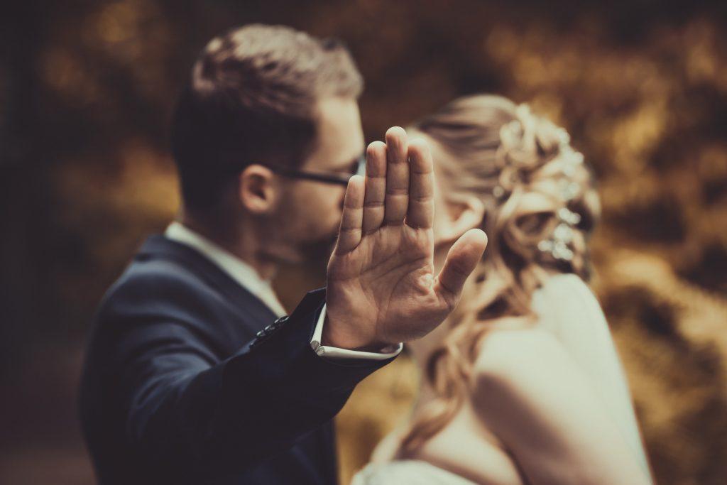 Brautpaar küsst sich während der Mann eine Hand davor hält
